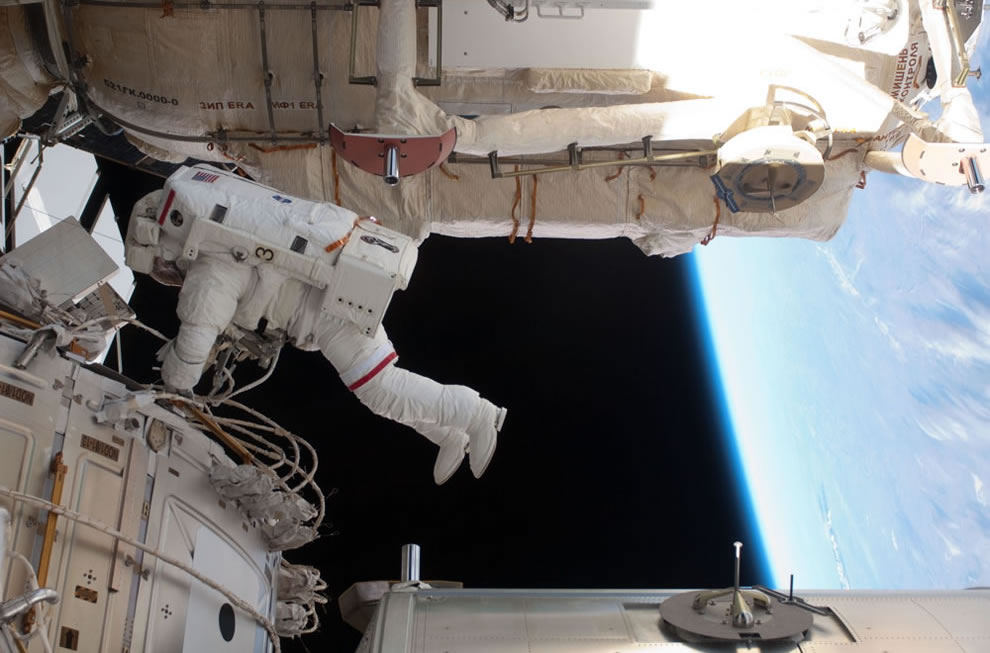 NASA astronaut Andrew Feustel is seen working while various components of the ISS are in view