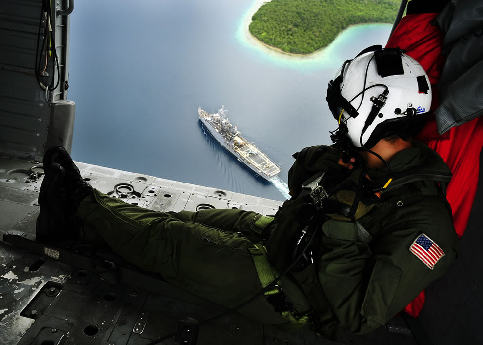 U.S. Navy Naval Air Crewman 2nd Class Bowen Derik, right, attached to Helicopter Sea Combat Squadron 23 watches the amphibious transport dock ship USS Cleveland
