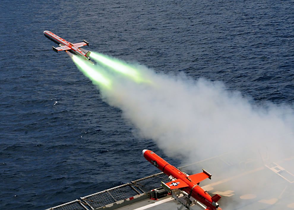 A BQM-74E Chukar target drone equipped with jet-assisted takeoff packs launches from   the flight deck of USNS Amelia Earhart