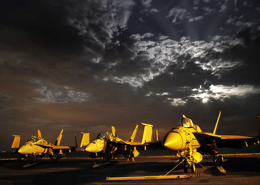 From left, a U.S. Marine Corps F/A-18C Hornet and two Navy F/A-18E-F Super Hornet  aircraft are illuminated by lights on board the aircraft carrier USS Enterprise as it transits the Suez Canal