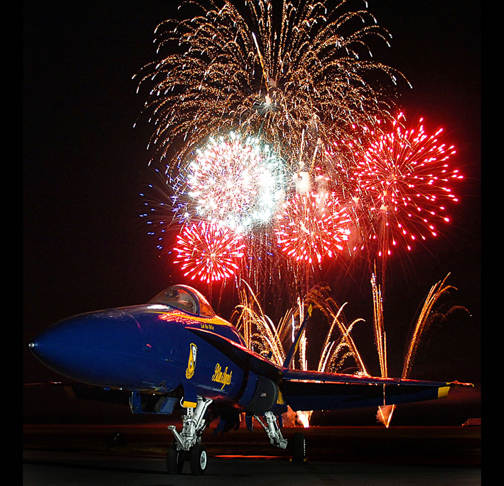 Fireworks explode and highlight an F/A-18A Hornet, assigned to the U.S. Navy flight   demonstration team, the Blue Angels, at the Mid-South Air Show at the Millington Municipal Airport