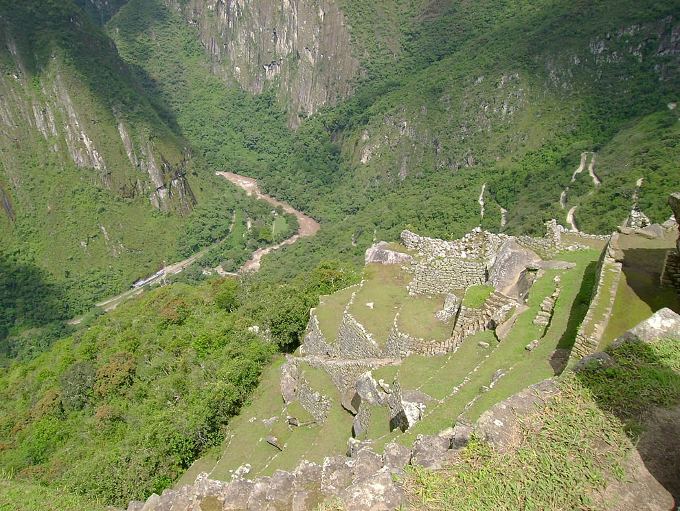 Machu Picchu is situated above a loop of the Urubamba River, which surrounds the site on three sides, with cliffs dropping vertically for 450 metres (1,480 ft) to the river at their base