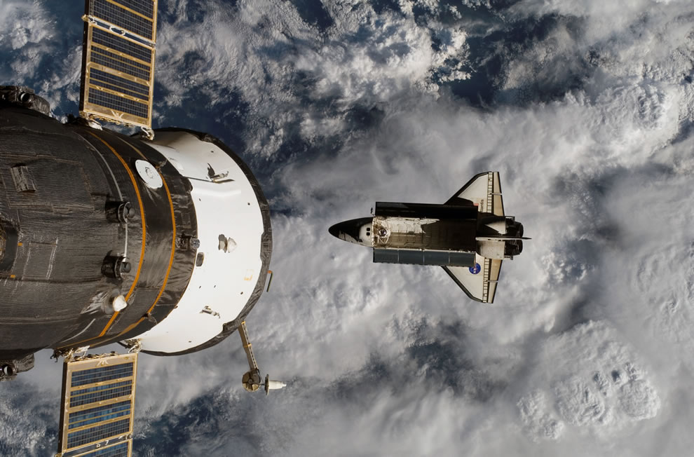 Backdropped by a cloud-covered part of Earth, Space Shuttle Atlantis was photographed by the Expedition 15 crew after it undocked from the International Space Station