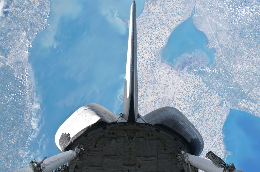 Backdropped over parts of Michigan and the Canadian province of Ontario, space shuttle Atlantis' vertical stabilizer, orbital maneuvering system (OMS) pods and aft payload bay