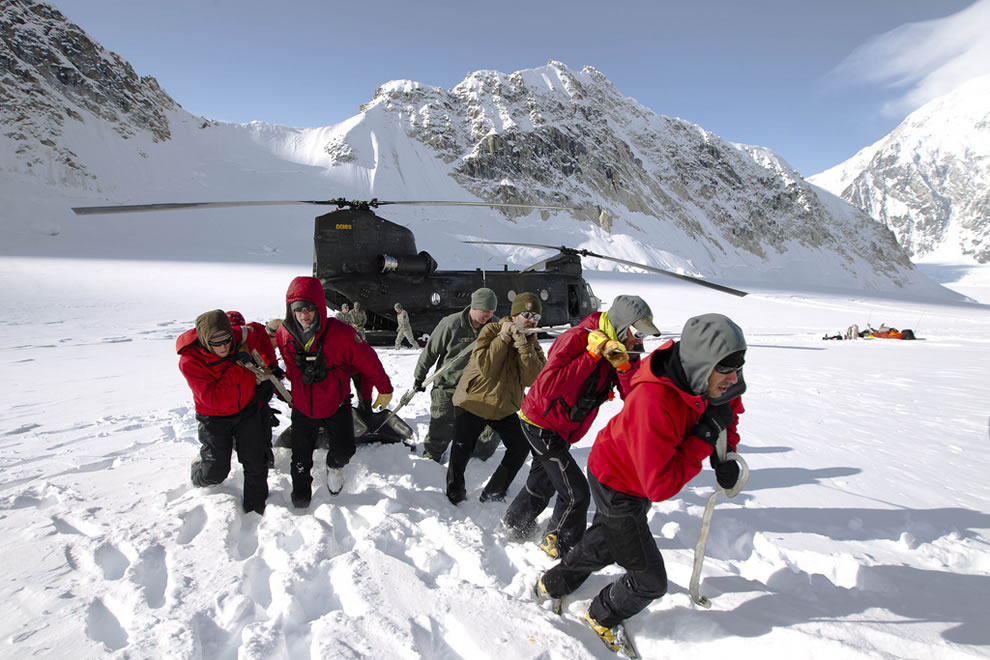 National Park Mountaineering Rangers unload survival equipment from a CH-47 Chinook on the Base Camp on the Lower Kahiltna Glacier