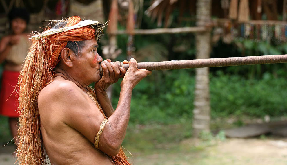 A Yagua (Yahua) tribeman demonstrating the use of blowgun (blow dart), at one of the Amazonian islands