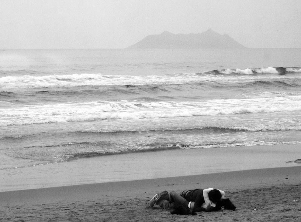 lovers kissing on deserted beach