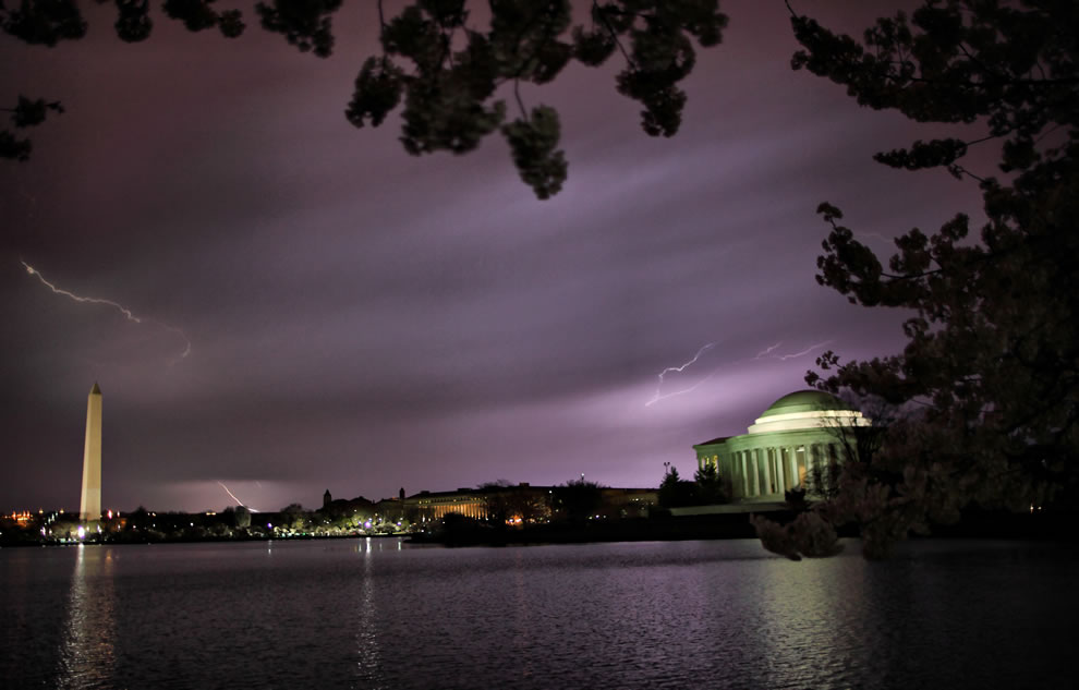 Lightning flashes over the Monument and the Jefferson memorial. Around the edges you can see the Cherry trees in full bloom