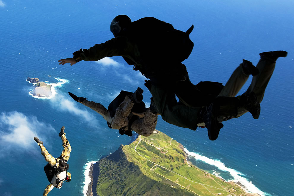 U.S. Air Force pararescuemen and Navy SEALs leap from the ramp of an Air Force C-17 transport aircraft during free-fall parachute training over Marine Corps Base Hawaii