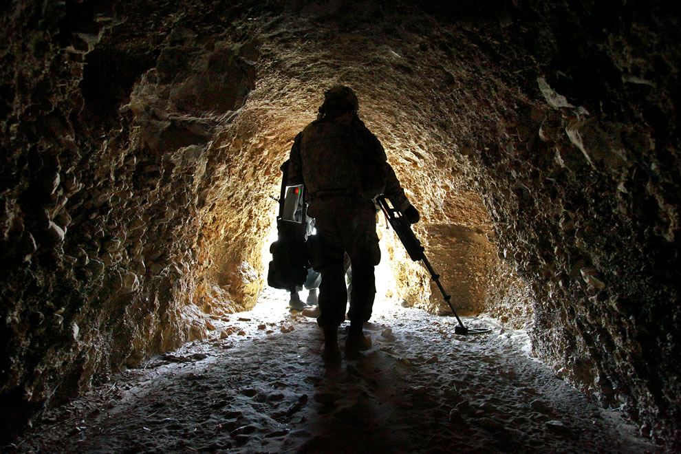 U.S. Army Spc. Jonathan Araiza uses a mine detector during a mission with Afghan police officers to search for enemy weapons caches