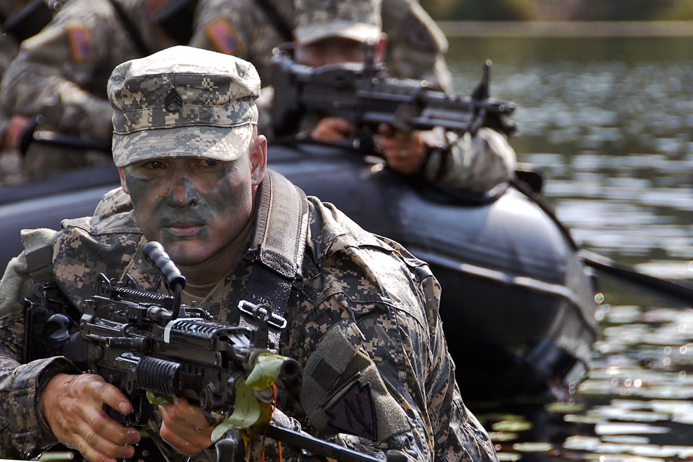 U.S. Army Staff Sgt. James Gibson scans the terrain while his battle buddies keep a watchful eye from the water