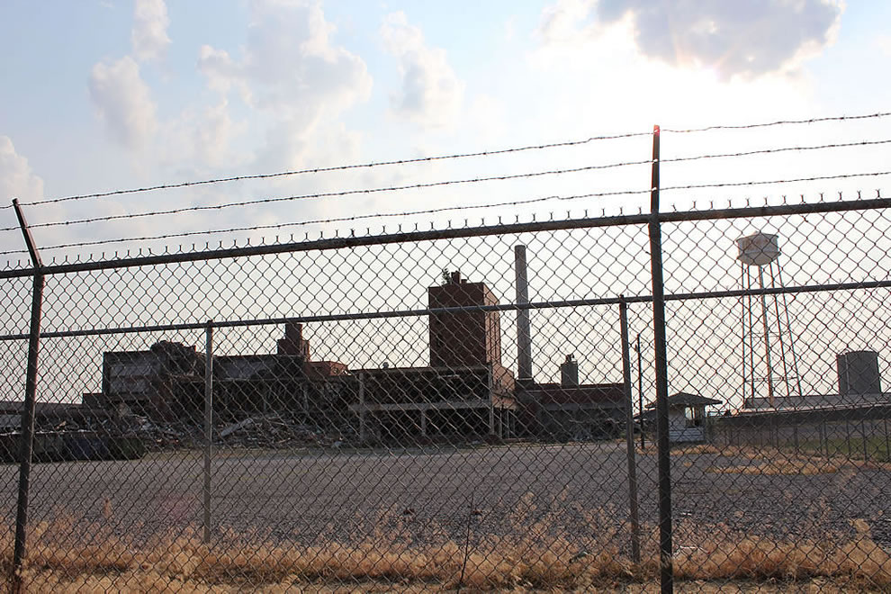 Barbed wire around defunct, burned, derelict, demolished Emge Food factory