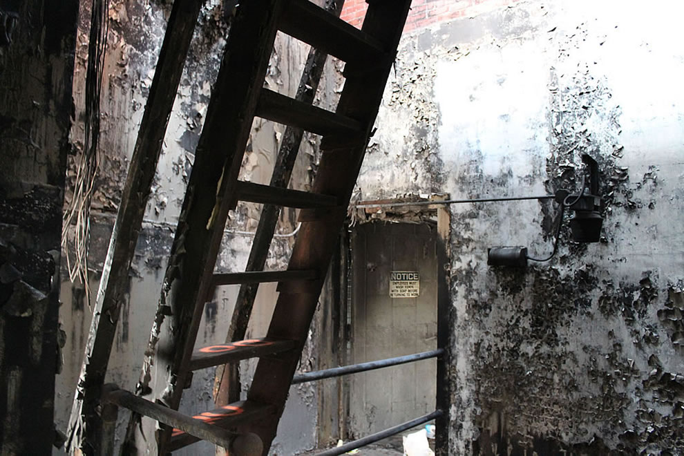 Burned stairs and sign at abandoned Emge Foods Plant