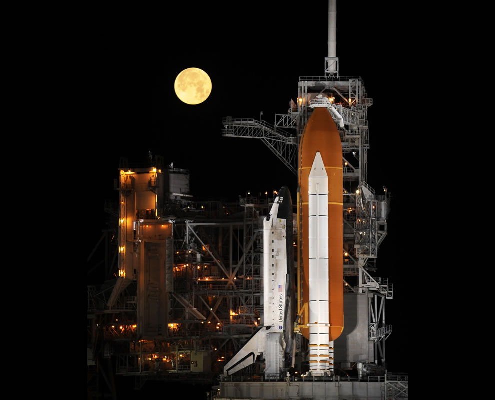A nearly full moon sets as the space shuttle Discovery sits atop Launch pad 39A at the Kennedy Space Center in Cape Canaveral, Florida, USA