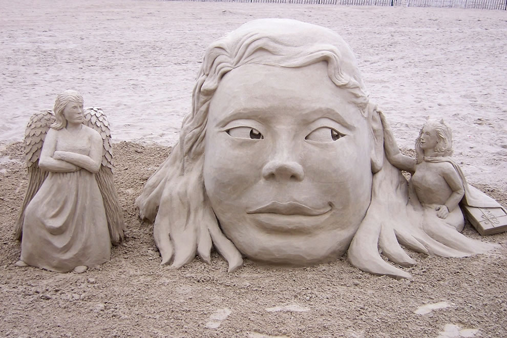 Sand Creations - This was temptation. A devil on one side with Godiva chocolates under her cape and an angered angel on the other. Hampton Beach, NH