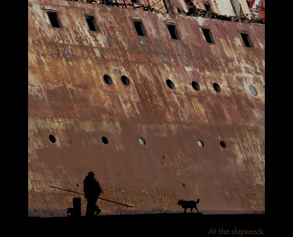 Upclose and in the shadows of a shipwreck Fisherman and his dog near left the Mikinay boat