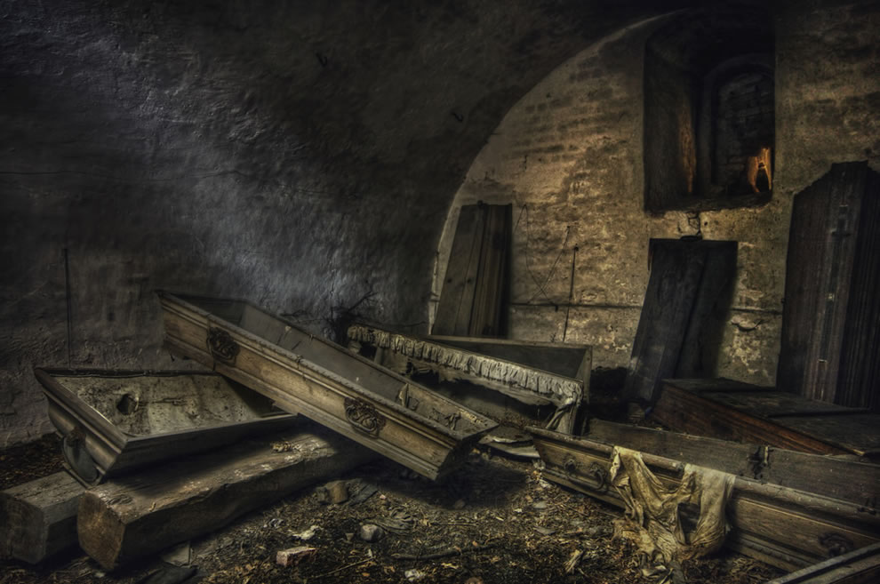 The black figure in an old abandoned crypt full of mostly empty coffins