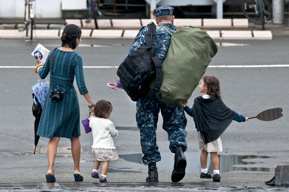 Military personnel leaves with his family after returning from summer patrol