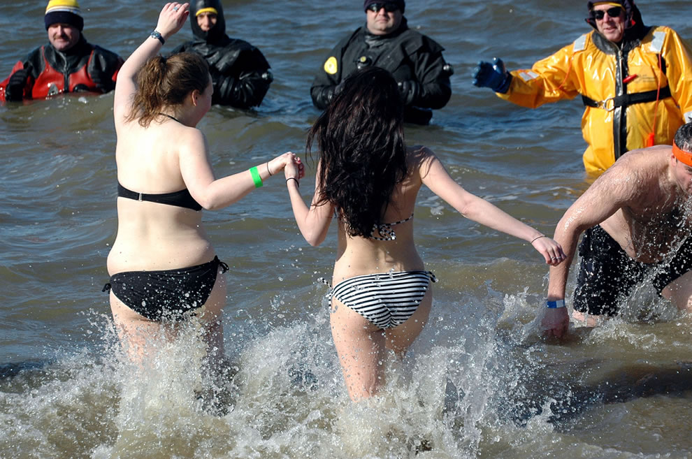 Holding hands for body heat during polar bear plunge in Indianapolis