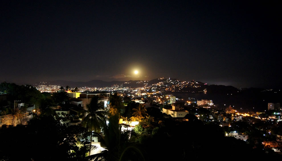 A bright moon rises over the clear night in Acapulco
