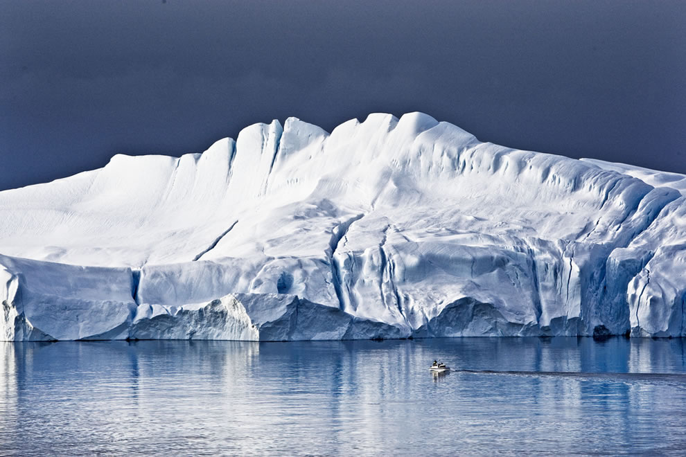 Feeling tiny in Greenland, small boat next to massively and majestic iceberg