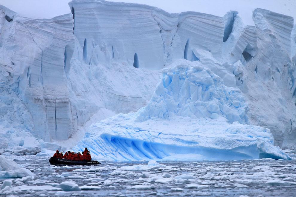Small boat in ice near immense icebergs in Antarctica