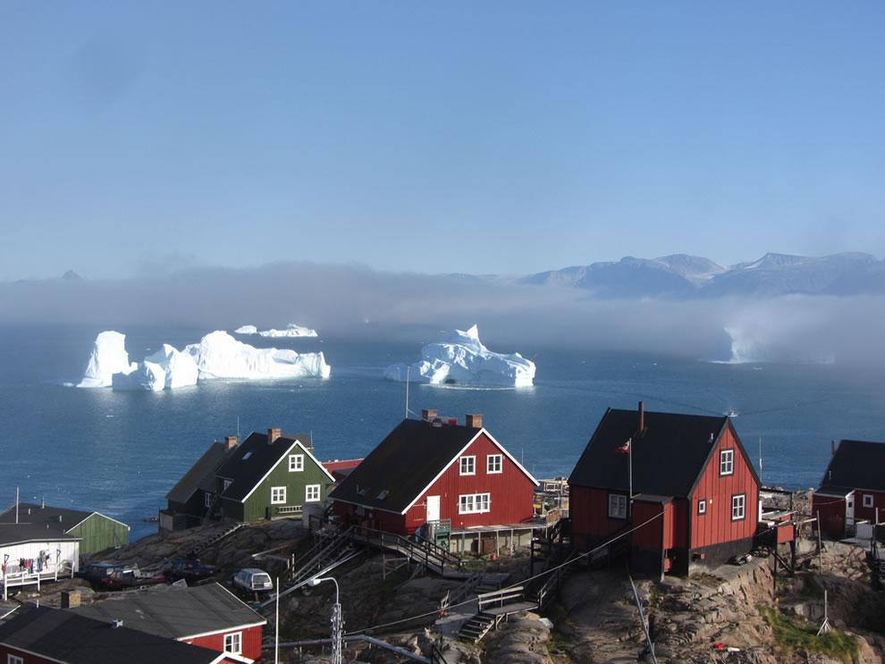 Uummannaq, North Greenland, houses overlooking icebergs in summer