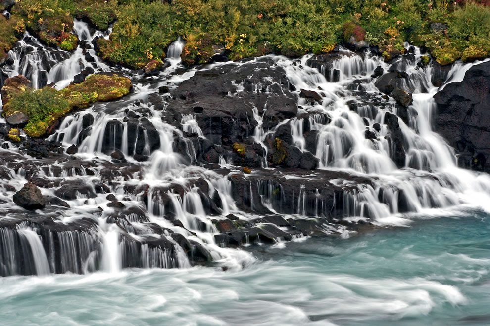 Close up of Hraunfossar, which means lava falls, and the blue stream that the waterfall feeds into the blue-colored river Hvitá
