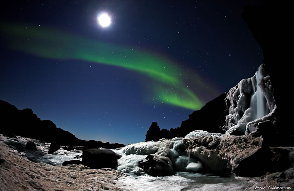 Moonshimmering Öxarárfoss waterfall and Aurora Borealis
