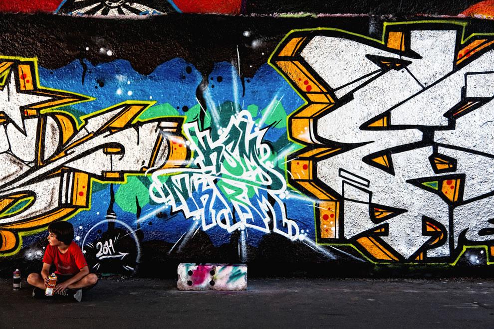Spray paint in hand, graffiti, boy tags wall