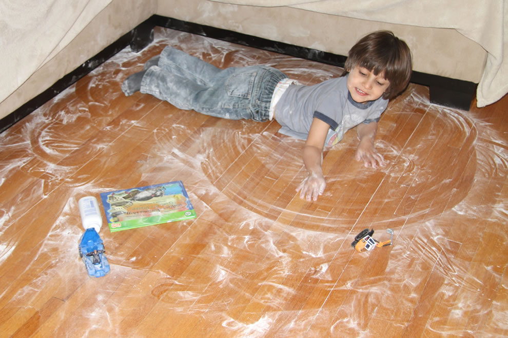 The Boy up to no good, smearing baby powder on the floor