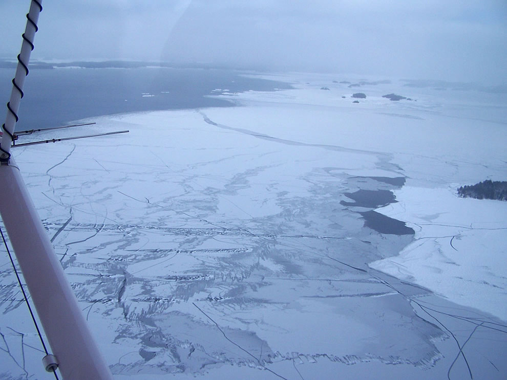 Aerial view of thin ice forming a shelf over open water on the lakes of Voyageurs National Park