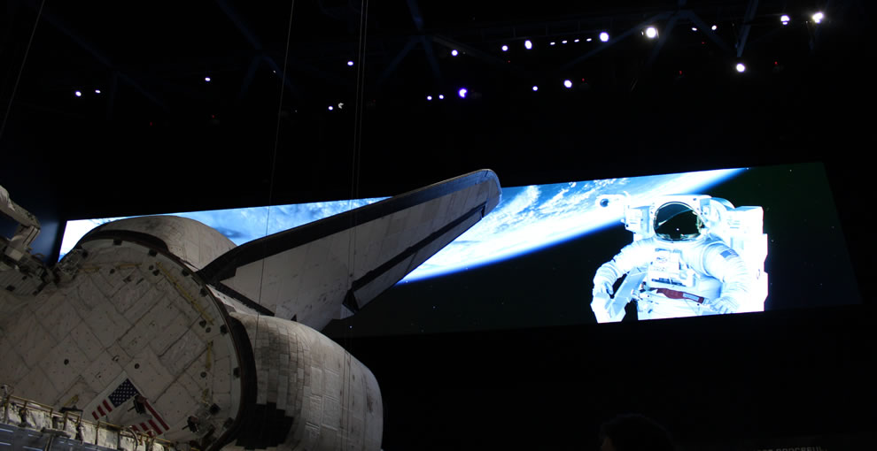 Atlantis, flag, astronaut on screen at Kennedy Space Center, Atlantis Space Shuttle exhibit