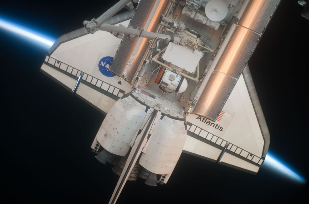 Intersecting the thin line of Earth's atmosphere, Space Shuttle Atlantis with payload bay doors open