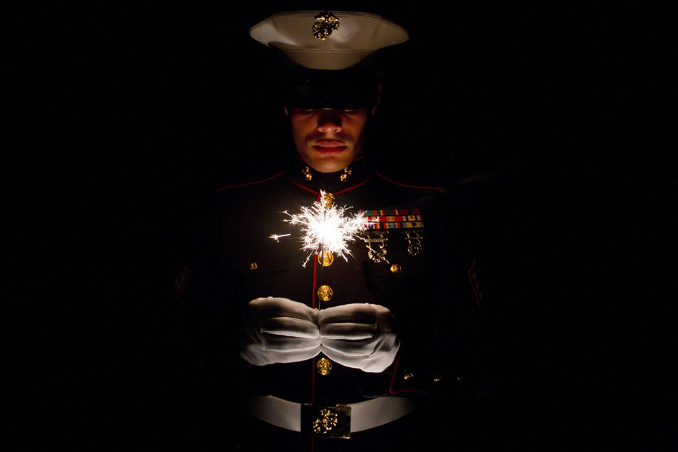 Marine holding a sparkler, celebrating July 4th
