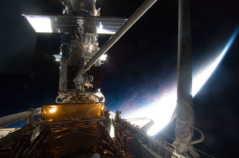 Riding Atlantis' remote manipulator system arm to the exact position to work on the Hubble Space Telescope