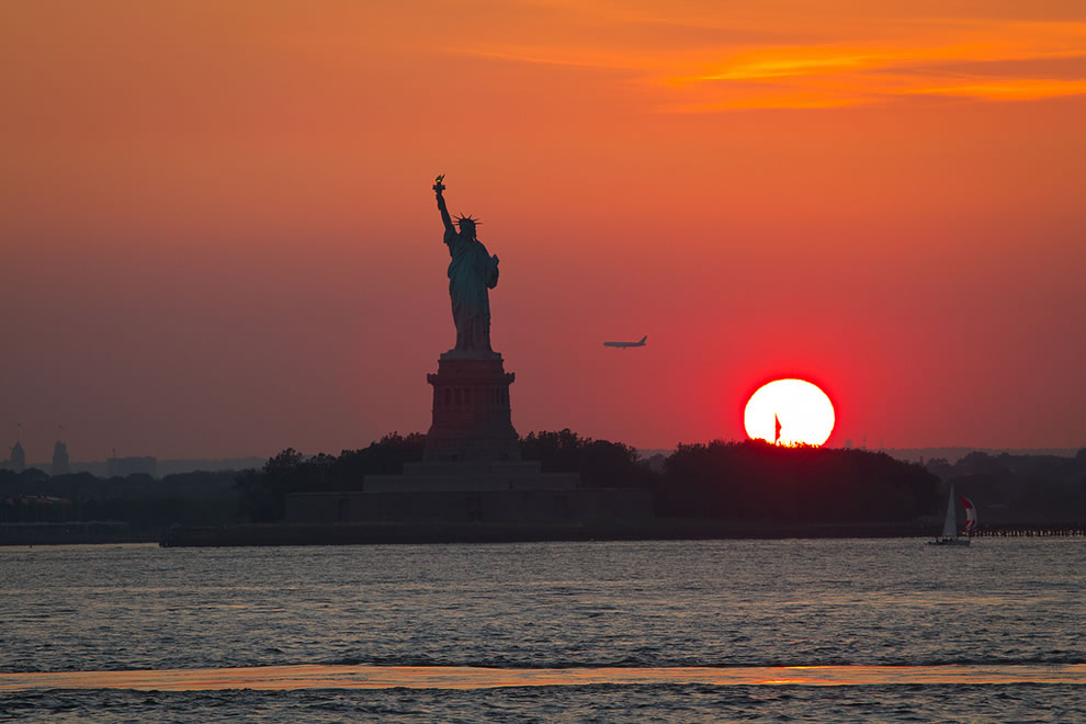 Sunset, jet, sailboat and Statue of Liberty