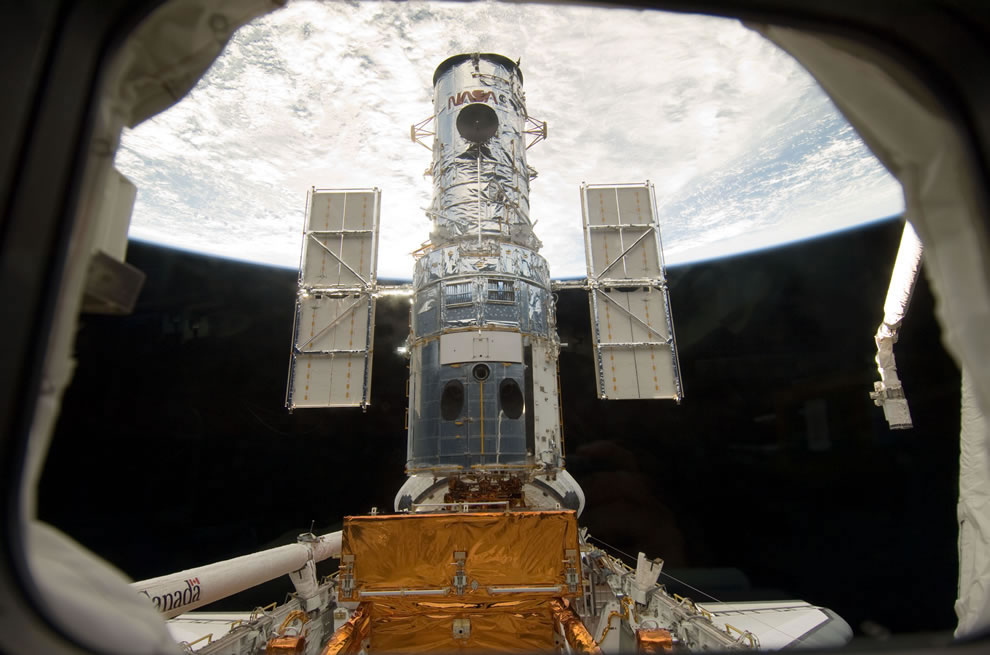 The Hubble Space Telescope stands tall in the cargo bay of the Space Shuttle Atlantis following its capture and lock-down in Earth orbit