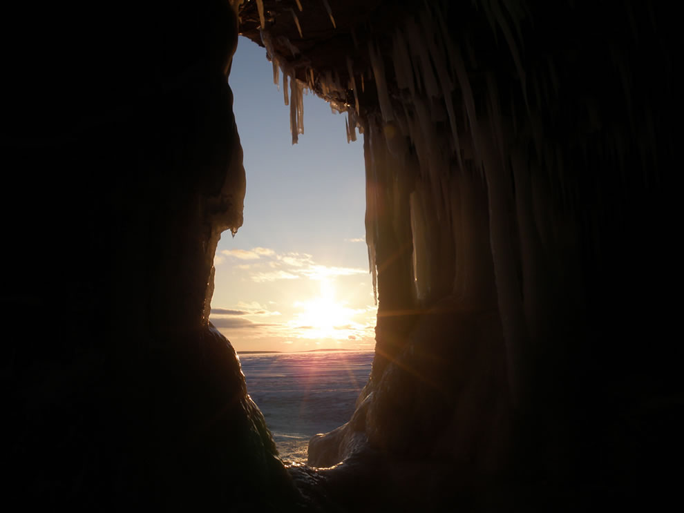 Looking out the ice cave at sun close to horizon over frozen Lake Superior