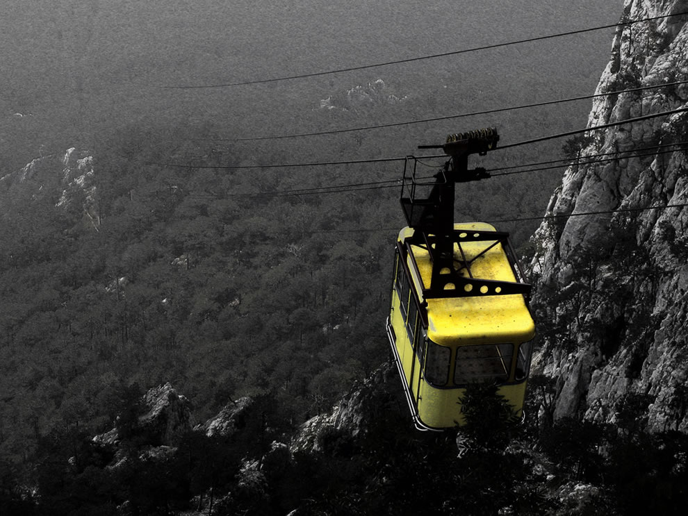 Different perspective in Crimea, yellow cable car over Yalta forest