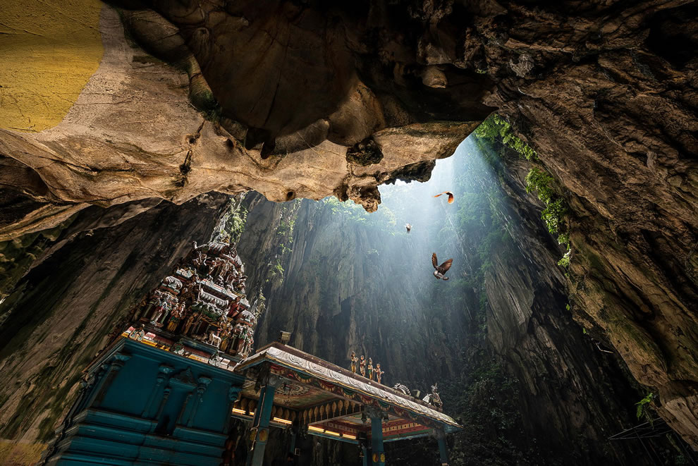 Birds, sunlight and a temple inside Batu Caves in Malaysia