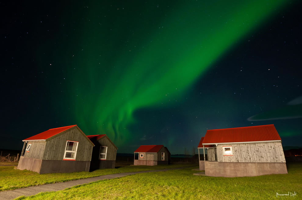 Northern lights over Iceland's red-roofed cabins