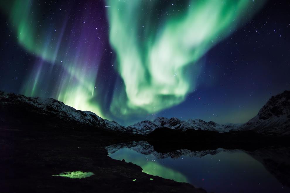 Northern lights over mountains and calm lake