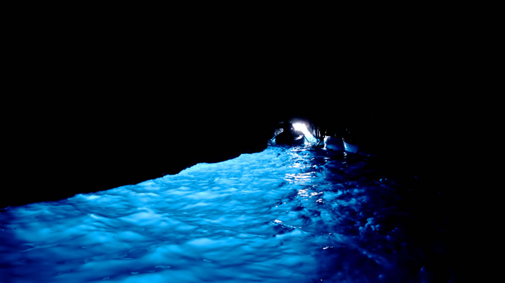 phosphorescent blue glow against pitch black sea cave